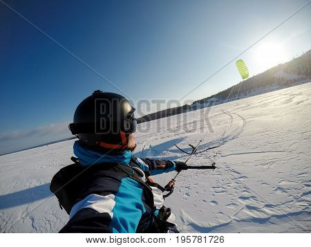 man athlete on alpine skiing with snowkite against a blue sky.