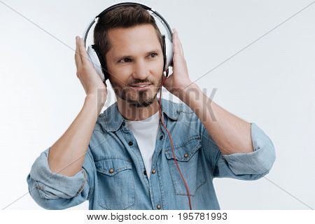 It suits me. Handsome man keeping smile on his face and putting hands on the headphones while standing over white background