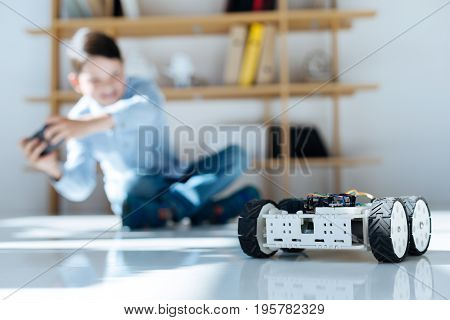 Happy gamer. The focus being on a white robotic vehicle moving across the floor while being controlled by a dark-haired little boy sitting on the floor and using a game controller