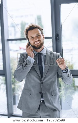 Portrait Of Young Excited Businessman Talking On Smartphone In Office