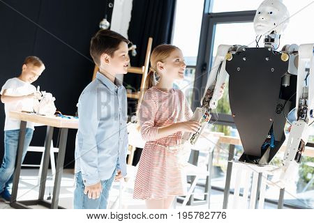 Awe-inspiring robot. Fascinated lovely children standing near a big human robot and checking out its work while the girl holding its hand