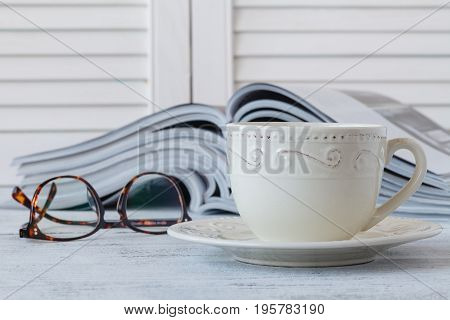 Cup Of Cappuccino With Magazine On Blur Coffee Shop Background