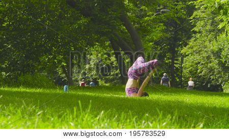 Young woman doing yoga exercises in the park. Padmasana