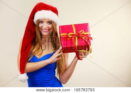 Woman In Santa Claus Hat Holds Gift Box. Christmas Time