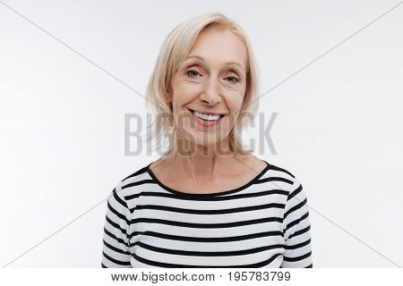 Trust me. Attractive female person keeping smile on her face and expressing positivity while standing over white background