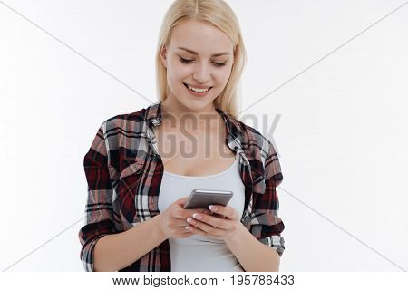 Wait for message. Delighted woman bowing head while keeping smile on face and standing isolated on white