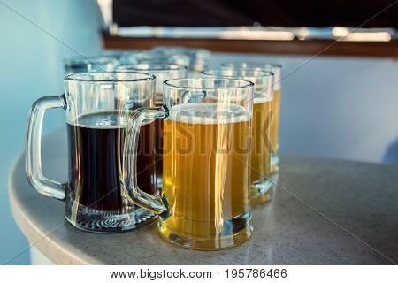 Jugs of dark and light beer placed on table placed on bar counter
