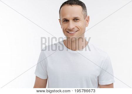 Delightful smile. Delighted male person standing over white background and keeping smile on his face, feeling happiness