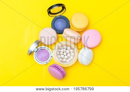 Composition of cosmetics and macaroons on a yellow background