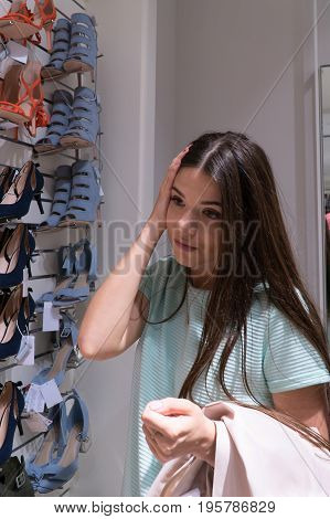 The girl chooses her shoes. The girl does not know what to choose.