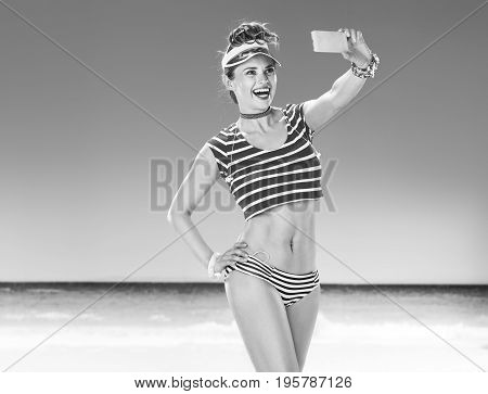 Smiling Fit Woman On Seacoast Taking Selfie With Mobile Phone
