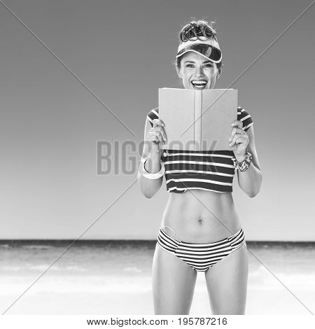 Smiling Healthy Woman In Red Sun Visor On Beach With Book