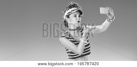 Woman Taking Selfie With Cellphone And Blowing Air Kiss