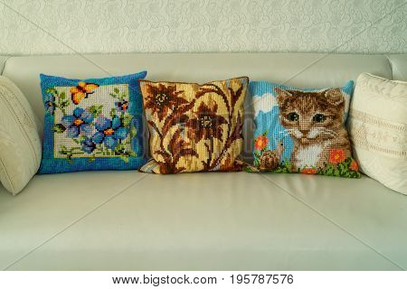 Close up three hand-made decorative cushions with embroidery on modern sofa
