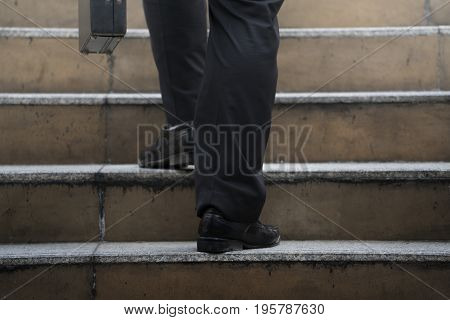 Businessman climbing up a concrete staircase concept on success