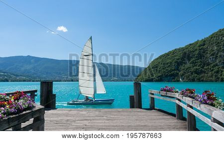 A beautiful white boat is sailing past a wooden dock on Lac d'Annecy in the South of France.