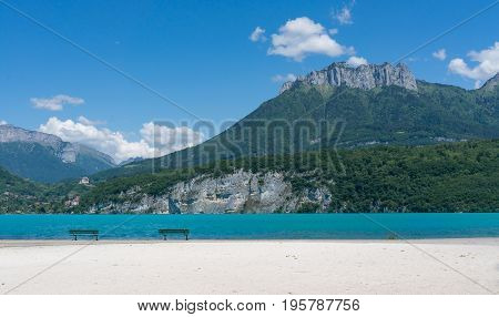Benches on the white sand in front of turquoise waters of Lac d'Annecy in the South of France beautiful mountain in the background.