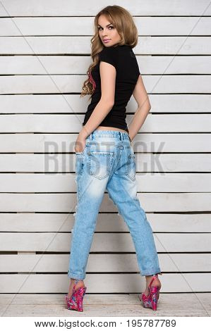 Young woman posing in blue jeans and black t-shirt near white wooden wall