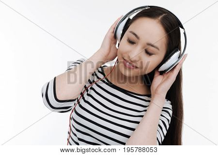 Tenderness in the air. Delighted longhaired brunette keeping eyes closed and bowing head while touching her headphones