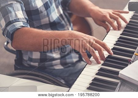 I can play. Invalid male person wearing checked shirt sitting before keyboard instrument while putting hands on it