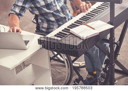Favorite work. Disabled male person wearing checked shirt sitting before keyboard instrument while putting hands on it