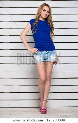 Young leggy blond woman in jeans shorts and blue t-shirt posing near the white wooden wall