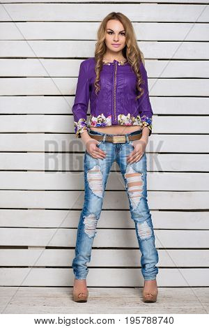 Young attractive blond woman in ripped jeans and purple jacket posing near the white wooden wall