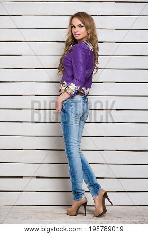 Slim blond woman in jeans and purple jacket posing near the white wooden wall