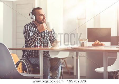 Let me think. Confident man wearing earphones looking aside while holding white cup in right hand