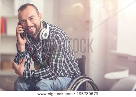 Call me tomorrow. Delighted young man sitting in wheelchair keeping headphones around his neck touching his elbow
