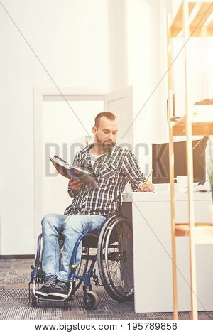 Collect information. Very attentive bearded man sitting in his wheelchair holding book in right hand while looking downwards