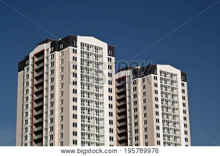 Two Residential Buildings In Front Of Blue Sky.