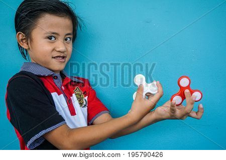 Keningau,Sabah-June 29,2017:Asian boy holds a spinners fidget in his hands in Keningau,Sabah.The occupational therapist research has seen fidget spinners help kids to concentrate in the classroom