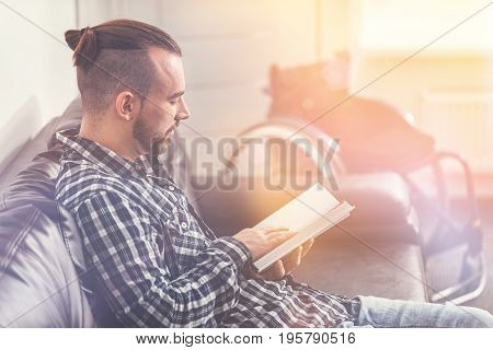 Prepare for exams. Very attentive man sitting in semi position on the comfortable sofa putting his right hand on the page while looking downwards