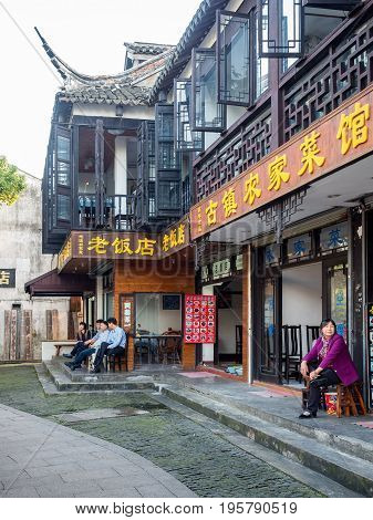 Suzhou, China - Nov 5, 2016: Restaurant and tea house in the historic Zhouzhuang Water Town. Some folks sitting outside the stores.