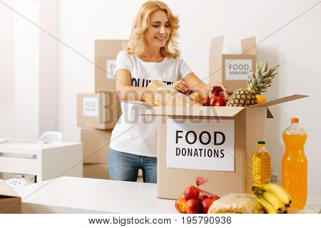 Arranging packages. Productive altruistic tender woman working pro bono while collecting a parcel with foods which people donating for charitable organization