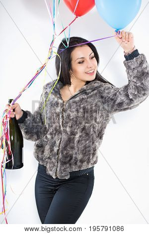 Portrait of smiling woman with a big bottle and balloons wearing furry jacket