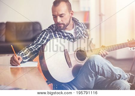 Not to forget. Delighted composer holding guitar on the leg turning his head to the table, sitting on wheelchair