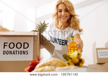 Essential supplies. Motivated productive passionate lady putting a bottle of oil into a box which her organization shipping to those in need