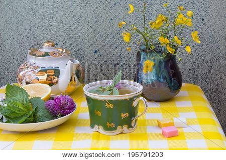 Teapot With Herbal Tea. Saucer With Fresh Mint Leaves, Clover Flowers And Lemon. Vintage Vase With W