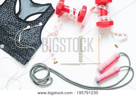 Creative top view of fitness and sport equipments with black notebook