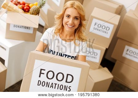 Spending free time right. Friendly cheerful admirable woman working for philanthropy organization and collecting donations while holding a box with food