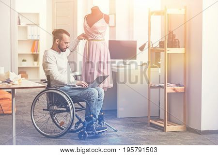 Talented stylist. Invalid designer sitting near dummy holding laptop on the legs while looking at screen keeping his hand near waist