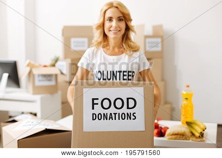 You can add something. Admirable young devoted lady holding a box full of food while working pro bono and packing parcels for shipment