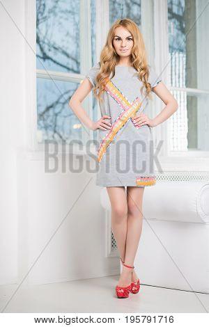 Nice blond woman posing in short gray dress near the window