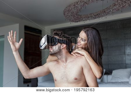 Young naked couple playing with VR glasses at home virtual reality