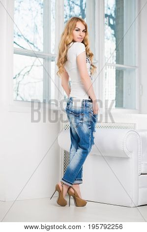 Young pretty blond woman posing in blue jeans and white t-shirt near the window