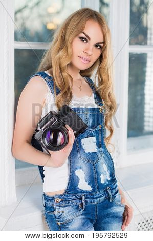 Portrait of young woman wearing ragged denim overalls posing with camera