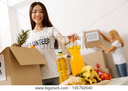 Putting all together. Hardworking remarkable smart lady picking a bottle while preparing a parcel with foods for shipping it to those in need
