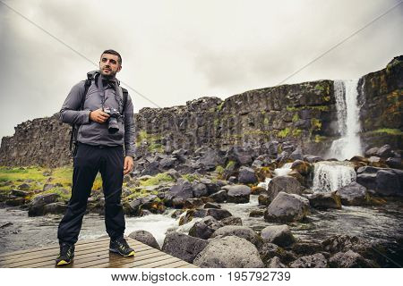 Young landscape photographer at waterfall at Pingvellir National Park.Photographing tectonic divide in Iceland between Eurasian and North American Continental plate and Oxararfoss fall in Thingvellir.